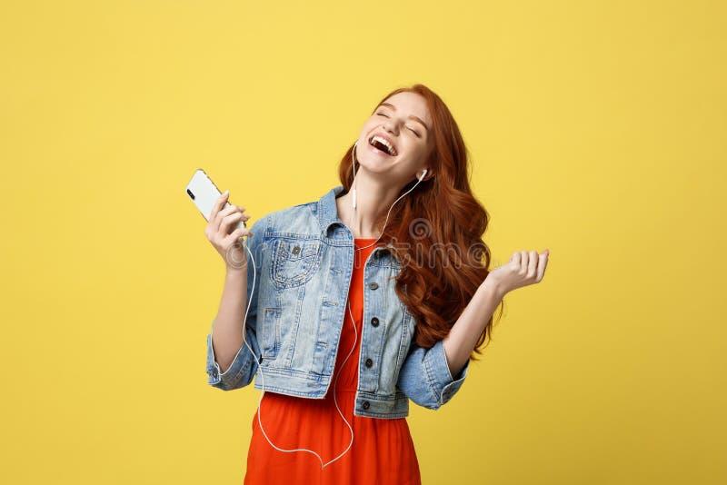 生活方式和音乐概念:耳机的美丽的年轻卷曲红色头发妇女听到音乐和跳舞在生动的 免版税图库摄影