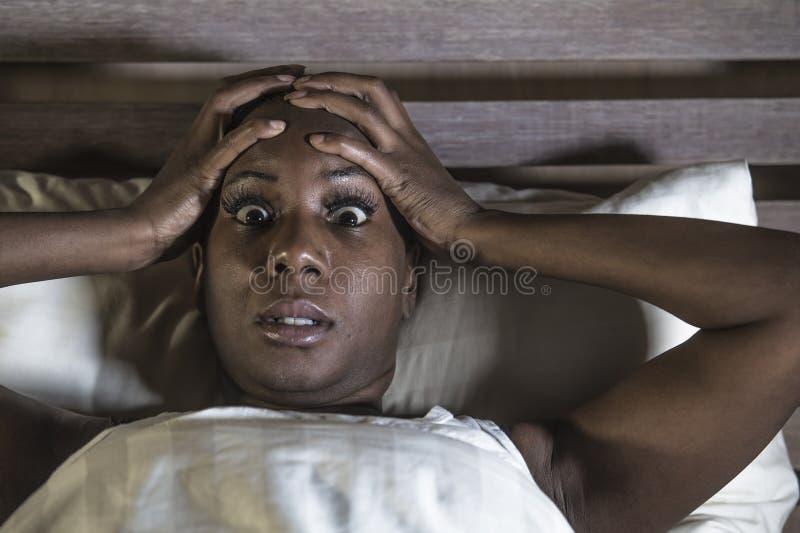 生活方式在床生气无法压下的年轻人害怕的和被注重的黑人美国黑人的妇女夜画象睡觉遭受的h 免版税图库摄影