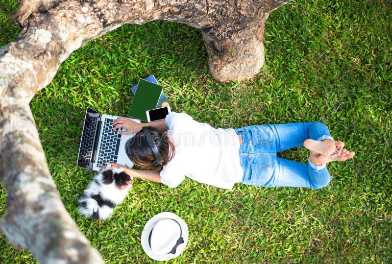 生活方式女孩早晨享用听的音乐和读书和戏剧膝上型计算机在自然公园的草地与 免版税库存照片