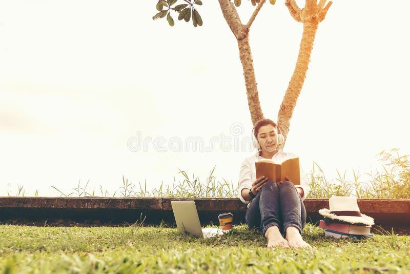 生活方式妇女享用听的音乐和读书和戏剧膝上型计算机在自然公园的草地,葡萄酒口气 库存图片