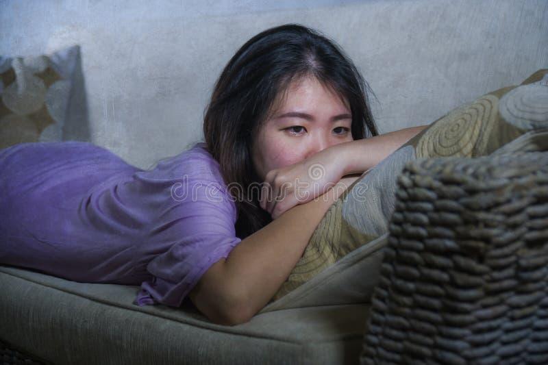 生活方式家庭长沙发画象年轻哀伤和沮丧的亚裔中国妇女哭泣的单独绝望和担心在痛苦痛苦 免版税库存照片