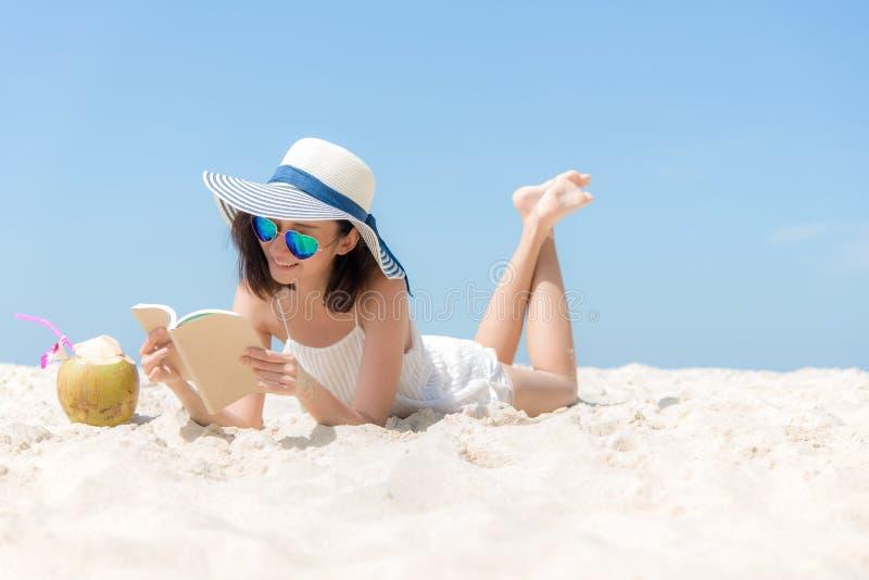 生活方式年轻亚裔妇女放松和读书在美丽的海滩在假日夏天, 图库摄影