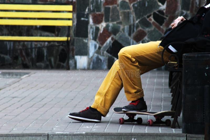 生活方式放松行家概念 放松在长凳的黄色牛仔裤的人溜冰板者 黄色长凳和石背景 图库摄影