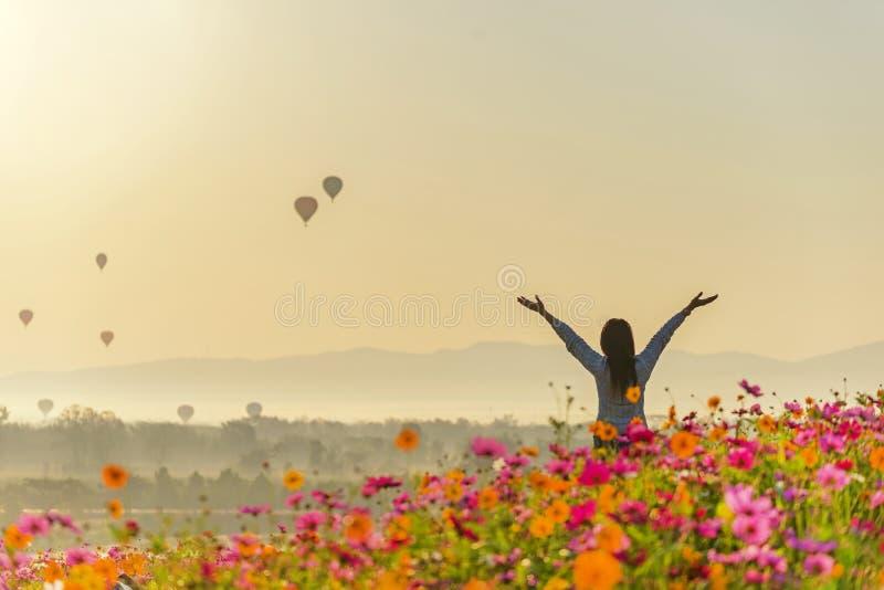 生活方式旅客妇女提高好手感觉放松和愉快的自由并且看见热气球 免版税库存照片
