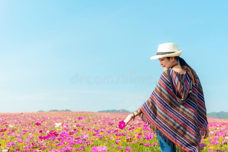 生活方式旅客妇女日出早晨提高好手感觉放松和在草甸自然波斯菊农场的愉快的自由 库存照片