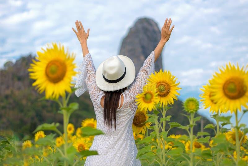 生活方式旅客或好旅游业妇女愉快的感觉放松和面对在自然向日葵农场的自由户外在sunr 库存照片