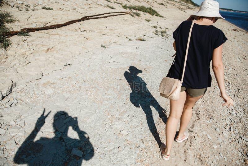 生活方式旅行概念 男性和女性去河岸在热的夏日 困难光 男性阴影陈列 库存照片