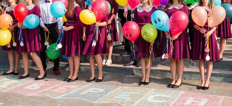生活方式概念高的学校毕业生在他们的手上拿着气球 免版税图库摄影