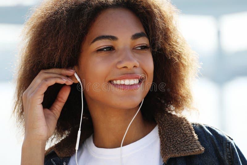 生活方式概念:使用手机和耳机的年轻非裔美国人的女孩,微笑 免版税库存图片