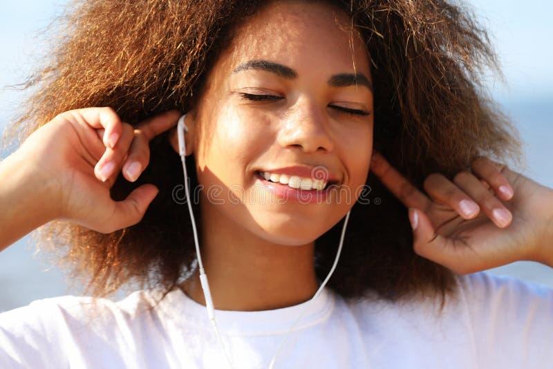 生活方式概念:使用手机的年轻非裔美国人的女孩 图库摄影