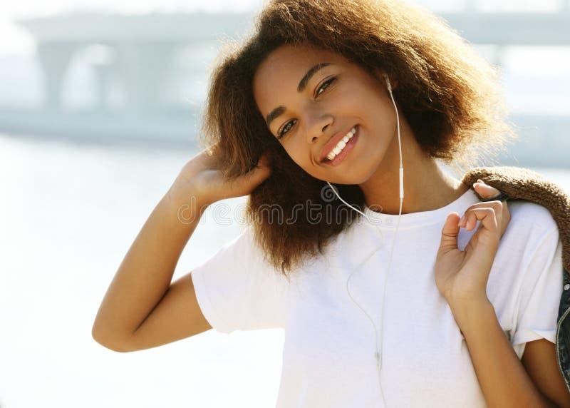 生活方式概念:使用手机的年轻非裔美国人的女孩 免版税图库摄影