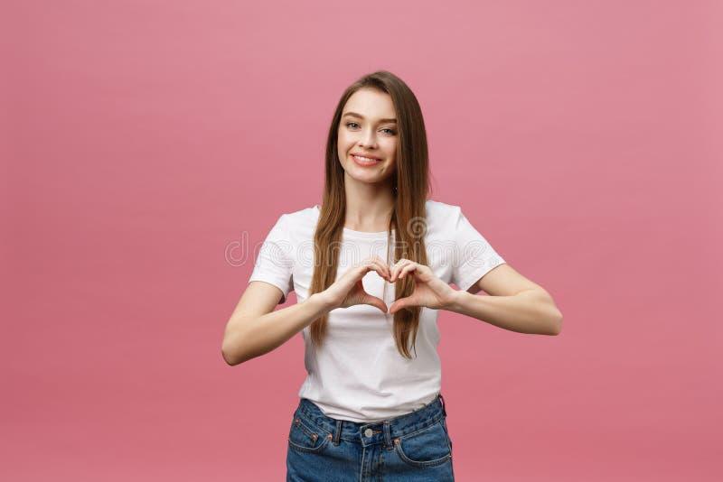 生活方式概念:做心脏标志用她的手的白色衬衫的美丽的可爱的妇女 库存照片