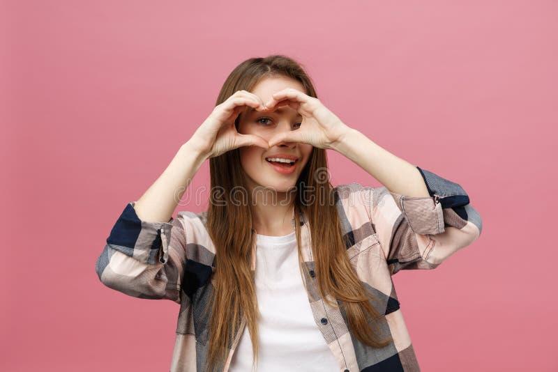生活方式概念:做心脏标志用她的手的白色衬衫的美丽的可爱的妇女 免版税库存图片