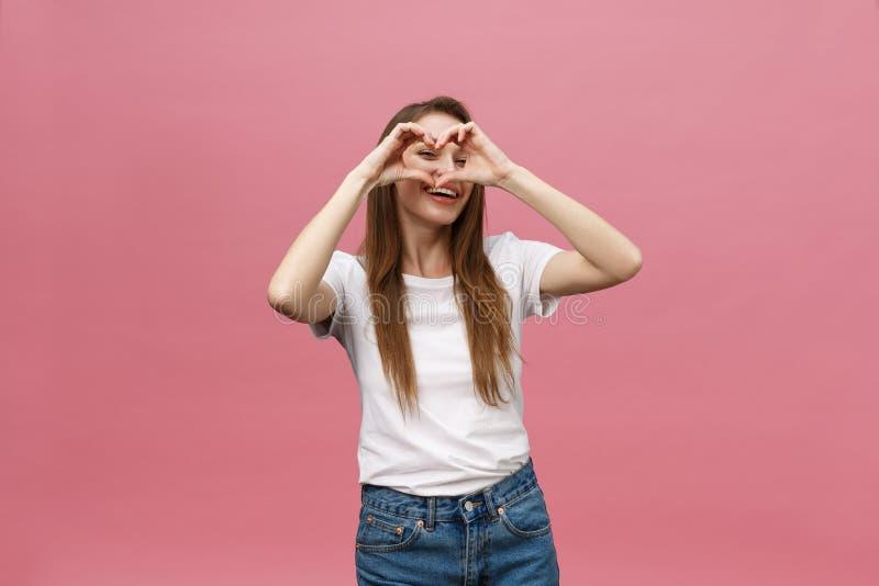 生活方式概念:做心脏标志用她的手的白色衬衫的美丽的可爱的妇女 免版税库存照片