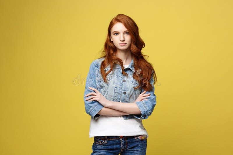 生活方式概念:牛仔布夹克的年轻白种人美丽的妇女横渡了胳膊-被隔绝在明亮的黄色backgroun 库存照片
