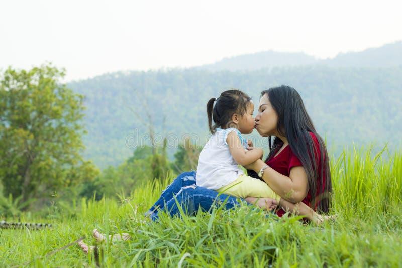生活方式画象妈妈和女儿幸福的至多在草甸,滑稽的亚洲家庭在米领域 免版税库存图片