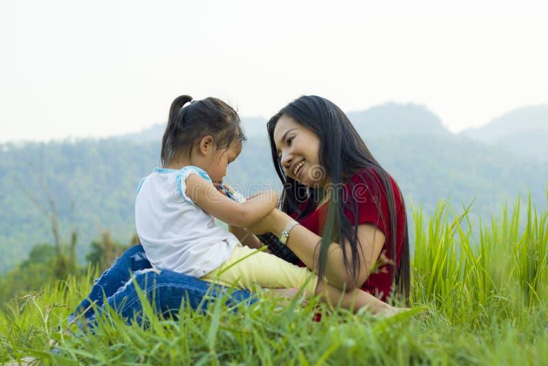生活方式画象妈妈和女儿幸福的至多在草甸,滑稽的亚洲家庭在米领域 免版税库存照片