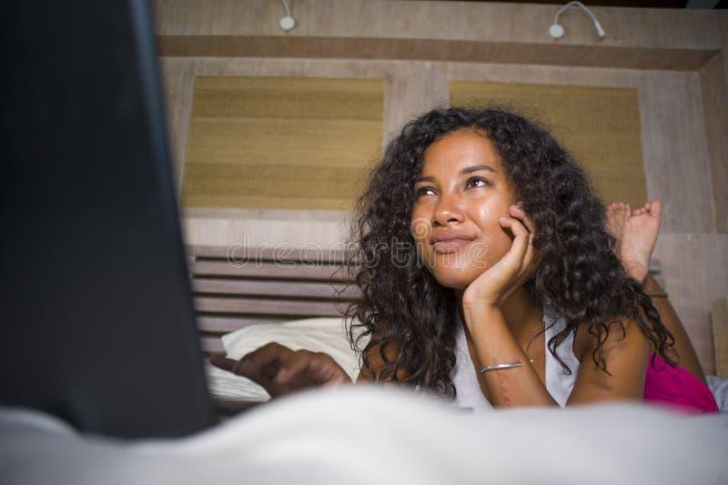 生活方式画象年轻美好和愉快黑非裔美国人妇女在家卧室说谎快乐在床网络usin 库存图片