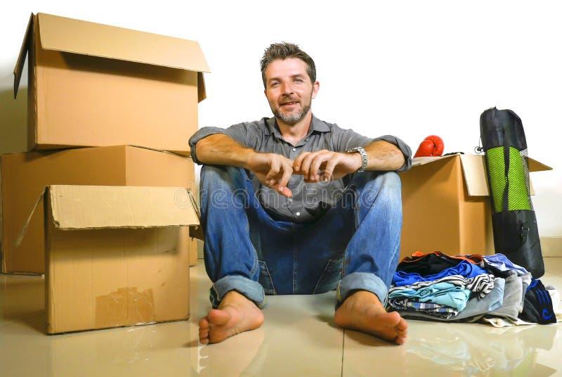 生活方式画象打开纸板箱和财产的年轻愉快和可爱的人单独移动向新的公寓  免版税库存图片