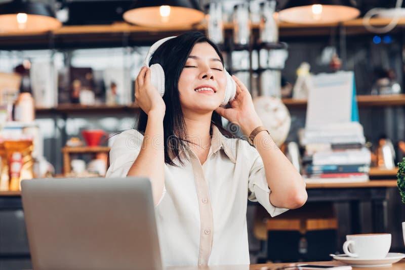生活方式自由职业者的妇女他使用耳机听的音乐dur 库存图片