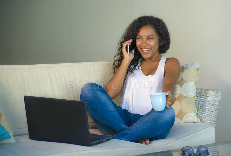 生活方式隔绝了年轻愉快和华美的黑人非裔美国人的妇女画象谈话在手机,当工作在lapt时 库存图片