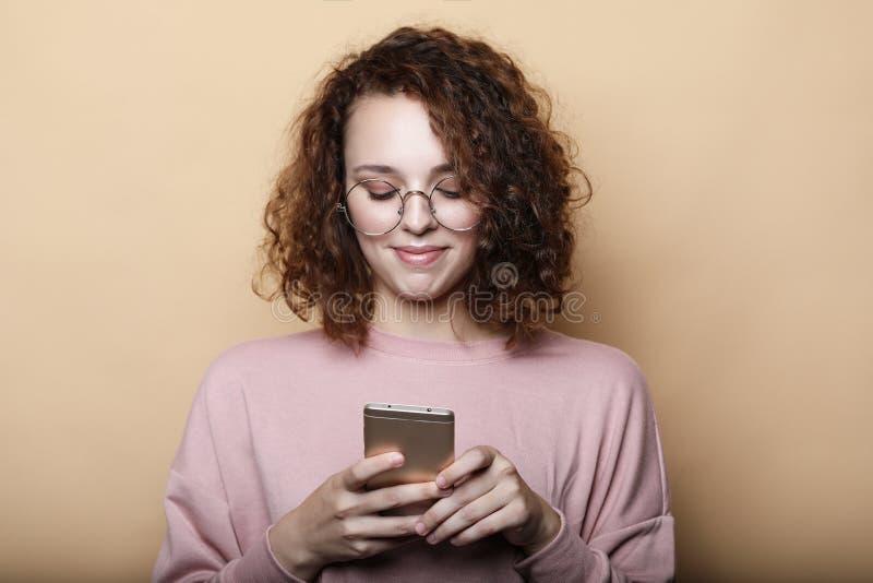 生活方式,情感和人概念:有巧妙的电话的,关闭年轻美丽的卷曲妇女 免版税库存照片
