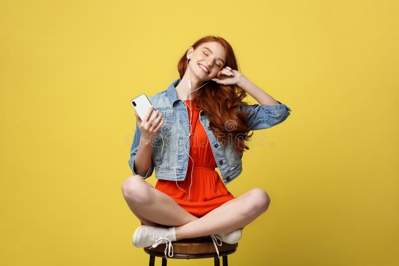 生活方式,音乐,技术概念:年轻美丽的白种人与耳机和巧妙的电话的妇女听的音乐 图库摄影