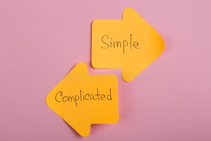 生活选择-以索引箭头的形式橙色贴纸与文本复杂和简单在桃红色背景 免版税库存照片