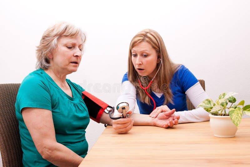 医生测量资深成人血压 图库摄影