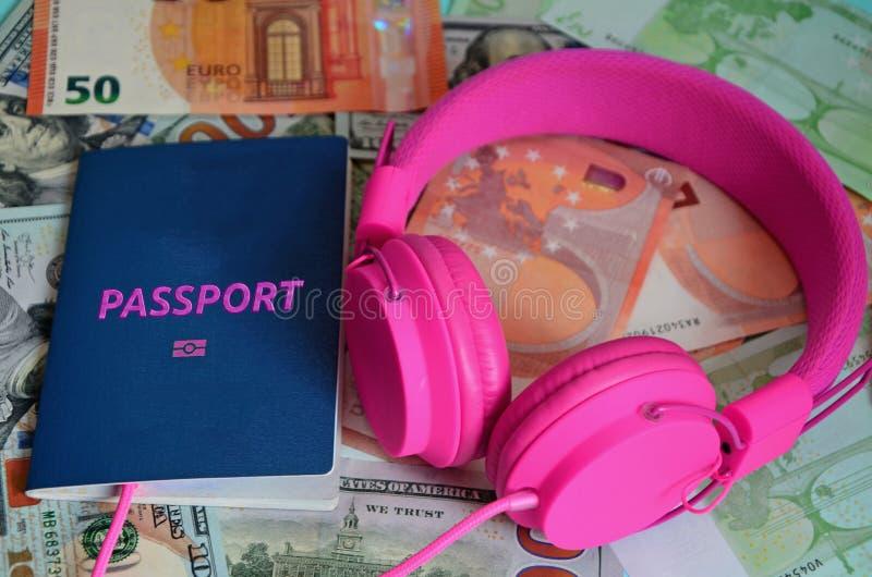 生物统计的护照和桃红色耳机在欧元和美元纸币背景说谎  昂贵的假期,必要 库存照片