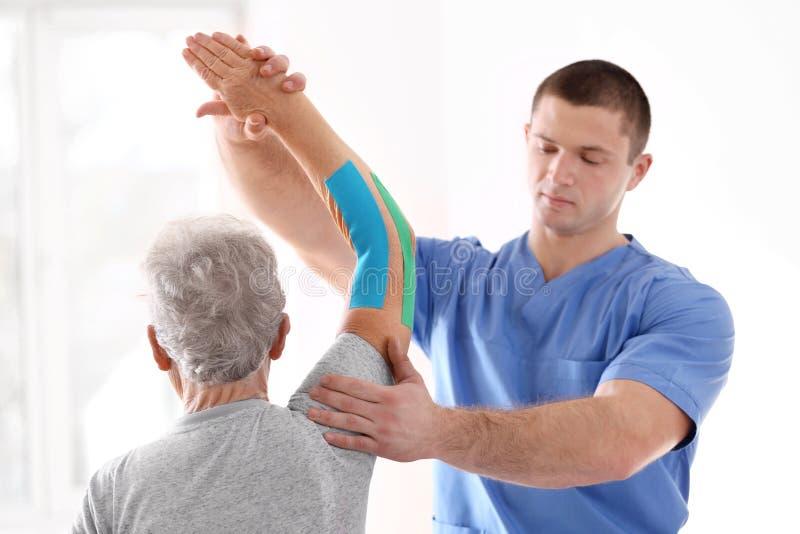 生理治疗师与诊所的年长患者一起使用 免版税库存照片