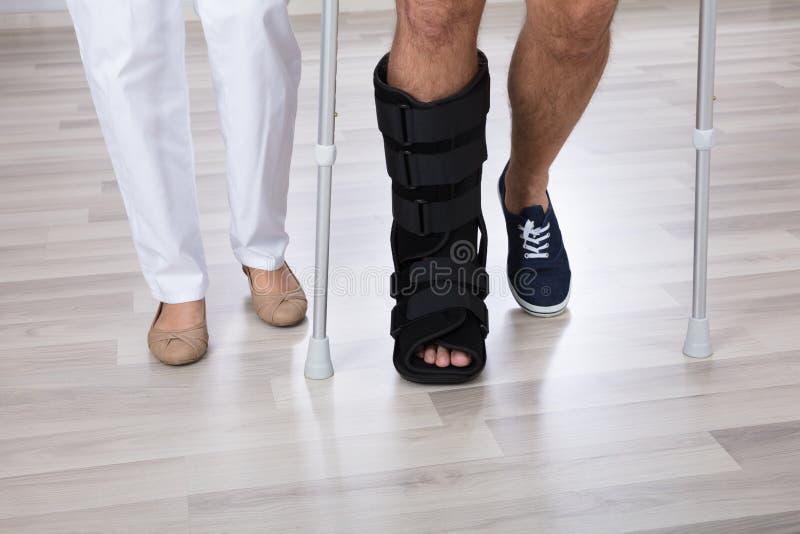 生理治疗师和受伤的人` s腿低部分视图  库存照片