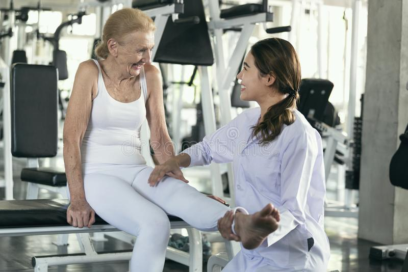生理治疗师在物理中心的帮助老资深妇女 年长健康生活方式概念 免版税库存照片