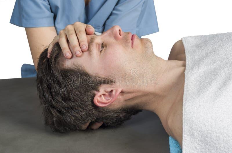 生理治疗师,做一种头盖骨荐骨的疗法的按摩医生 图库摄影