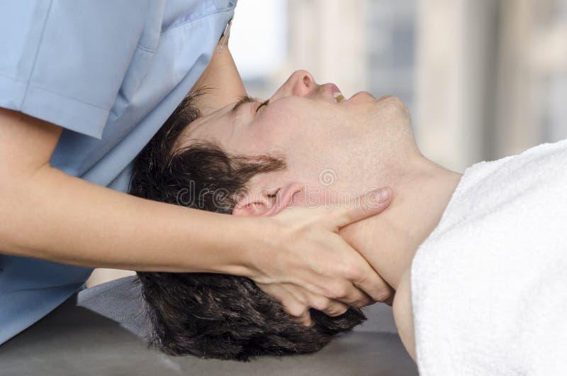 生理治疗师,按摩医生做着操作子宫颈 免版税库存照片
