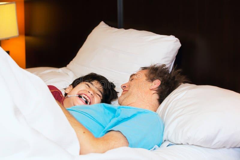 生睡觉在与残疾年轻儿子的床上,笑和smi 库存图片