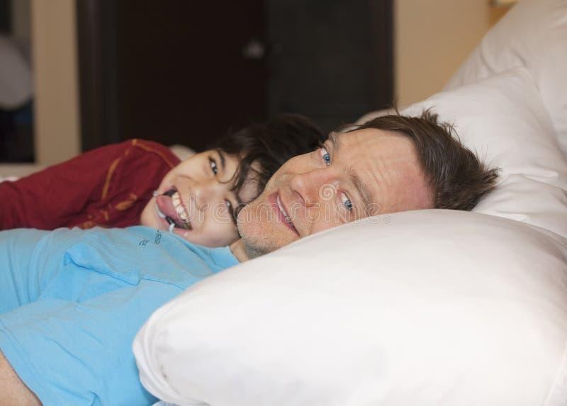 生睡觉在与残疾年轻儿子的床上,笑和smi 库存照片