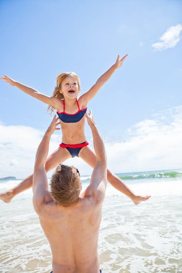 生空气的投掷的年轻女儿在海滩 免版税库存照片