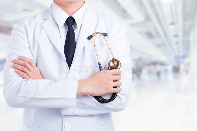医生立场折叠你的胳膊有听诊器办公室背景 免版税库存图片