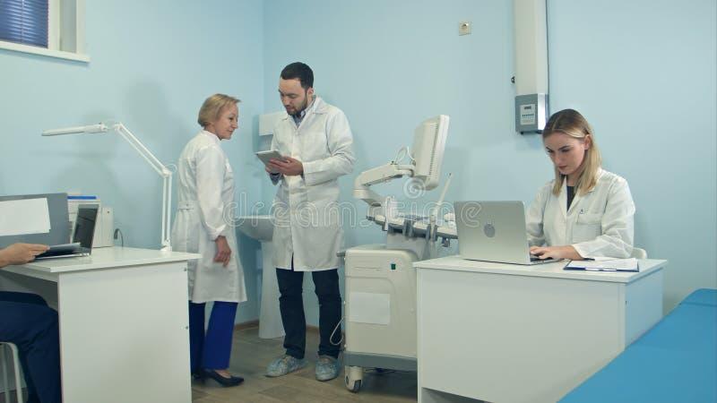 医生繁忙工作在使用膝上型计算机和片剂的办公室 免版税库存照片