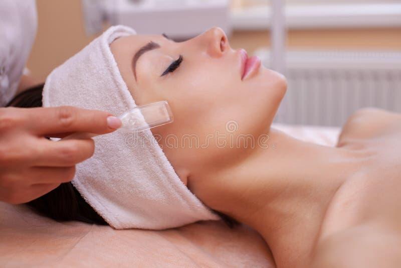 医生美容师做做法真空面孔清洁一个美丽,少妇 免版税库存图片