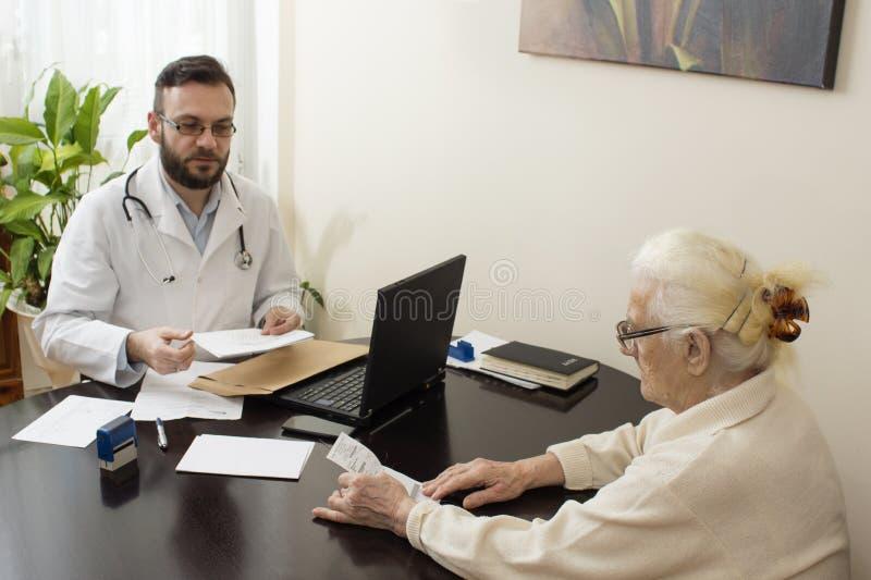 医生老年医学专家的老妇人 有一名患者的老年医学专家医生在他的办公室 免版税库存图片