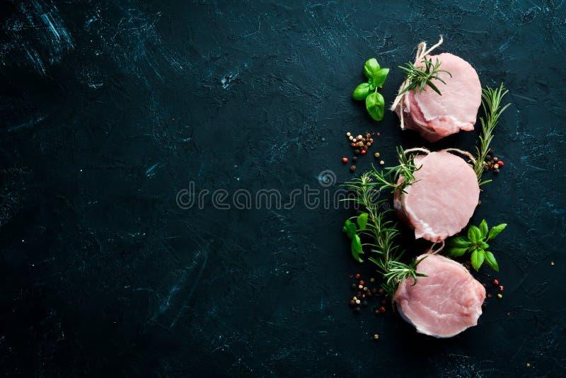 生肉、大奖章用迷迭香和香料 在黑石背景 图库摄影
