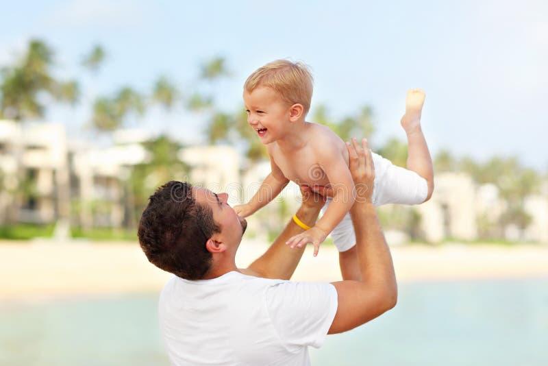生获得在海滩的乐趣与他的小儿子 库存图片