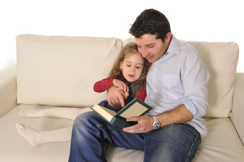 生讲童话给逗人喜爱的矮小的女儿 免版税库存照片