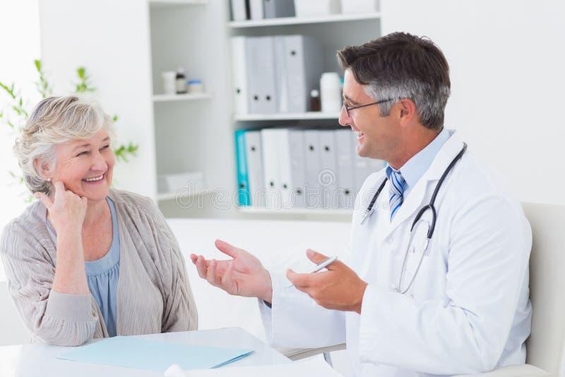 医生谈论与资深患者在桌上 免版税库存图片