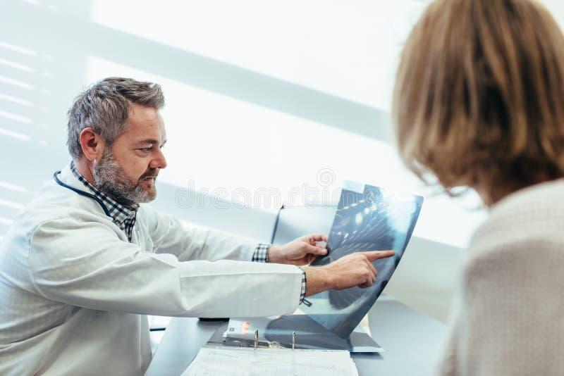 医生谈论医疗扫描结果与患者 库存图片