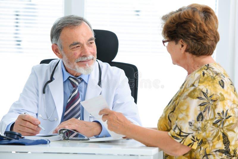 医生谈话与他的女性患者 库存图片