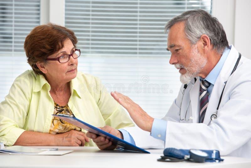 医生谈话与他的女性患者 免版税库存照片