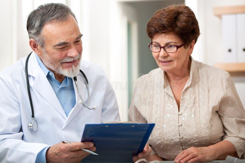 医生谈话与他的女性资深患者 免版税库存照片